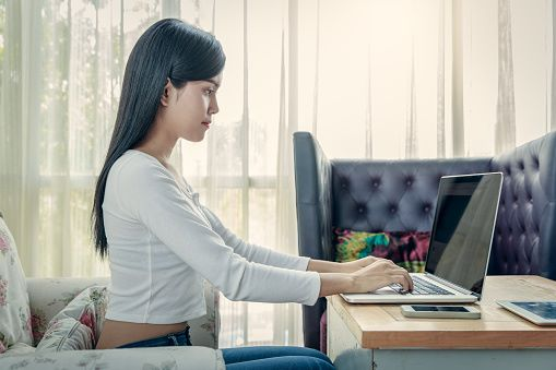 Woman sitting at laptop with good posture
